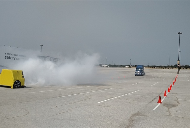Tractor with OnGuard Active begins its run toward smoke, much like what wild fires sometimes send across highways. Here it obscures an inflatable car sitting in the truck's lane. Test speed was 18-19 mph.