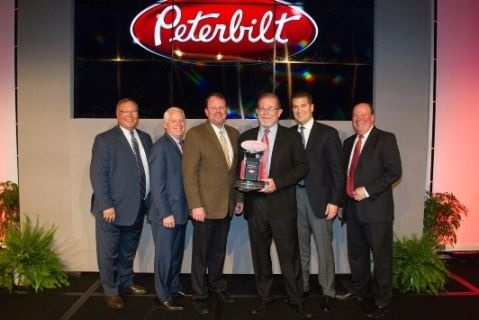 "Rush Enterprises' chairman, CEO and president W.M. ""Rusty"" Rush, senior vice president and COO Michael J. McRoberts, senior vice present – Peterbilt Dealerships Corey H. Lowe and senior vice president of Retail Sales James E. Thor accepted the award during Peterbilt's annual Dealer Meeting."