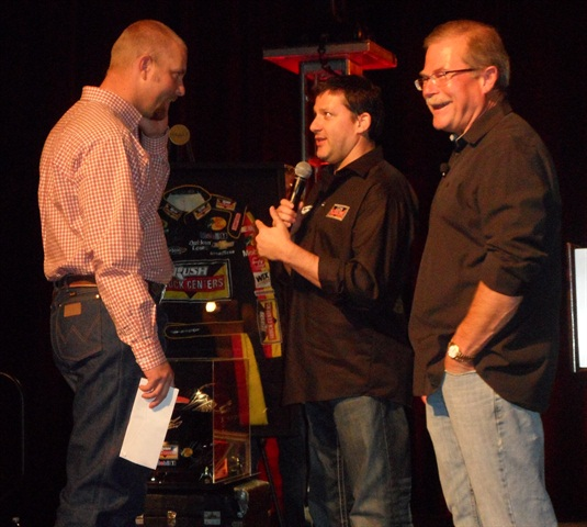 From left, All-Around Grand Champion Jason Swann is congratulated by NASCAR driver Tony Stewart and company Chairman Rusty Rush at the Tech Skills Rodeo banquet on Tuesday night. Building team spirit is part of the Rush culture.