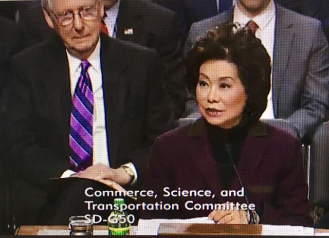 Elaine Chao at her Jan. 11 confirmation hearing. Looking on is her husband, Senate Majority Leader Mitch McConnell. Screenshot via Senate Commerce Committee