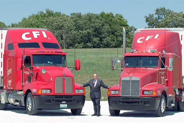 "The year before its acquisition by Con-way, CFI chairman and CEO Glenn Brown posed with the company's original Kenworth T600 (right) and a 2006 version, celebrating the ""Anteater's"" 20th anniversary. Photo courtesy Kenworth"