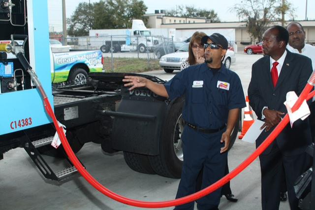 A fleet mechanic from Frito-Lay (center) demonstrates the compressed natural gas (CNG) fueling process to Orange County Commissioner Samuel Ings (right) at the amp Trillium CNG, LLC CNG grand opening  in the Princeton Industrial Park, near the Frito Lay Orlando Plant.