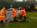 Photo of North Carolina highway crews digging trenches to drain a flooded road courtesy of NCDOT.