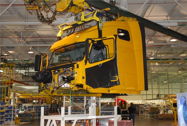 14. At a point where the two assembly lines merge, the cab is hoisted in the air and set gently down on the frame and is bolted in place. Electrical, air and liquid fittings are connected as the cab becomes one with the chassis.