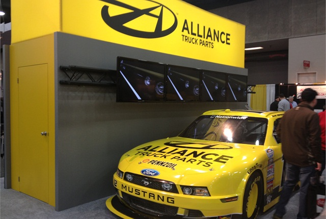 Alliance Truck Parts gets attention with their bright yellow and black color scheme and their sponsored race car at their booth.