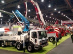 Concrete pumper trucks line aisles of the Las Vegas Convention Center's central hall, where most heavy truck displays are housed. Numerous mixer trucks are also here.