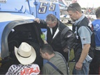 Craig Kruckeburg and the Minimizer pit crew check damage on the Ford