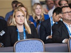 An attendee listens to a conference speaker.