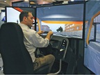 An attendee tries out the driver simulators at the Virage booth.