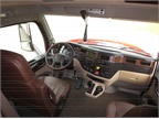Dark wood trim is applied to the dashboard and side-door panels. Brown