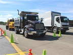 The T370 Dump and K270 Cabover van await their turns on the test