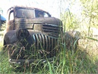 A massive-grilled old Chevy sits alone in the grass. Photo: Jack