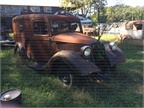 A  30s-vintage Ford sedan delivery van waits near the parking lot.
