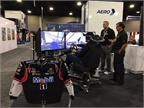 Enjoying a race simulator at the Mobil booth. Photo: Deborah Lockridge