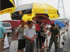 Truckers gather under umbrellas to watch the Shell roadshow